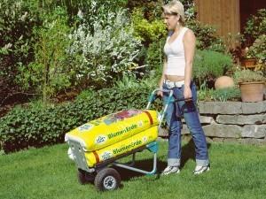 Frau tranportiert mit Wolfcraft Sackkarre Blumenerde im Garten