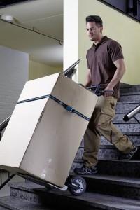 Mann transportiert mit einer Klappkarre einen Karton über eine Treppe.