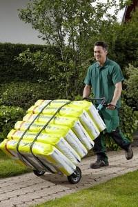 Gärtner transportiert mit Wolfcraft Klapsackkarre Blumenerdesäcke