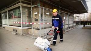 Mann transportiert mit Profi Karre Zementsäcke auf der Baustelle.