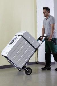 Ein Mann der mit einer Sackkarre die klappbar ist, eine Waschmaschine transportiert.