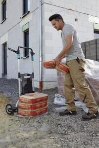 Mann belädt die Bau Sackkarre Wolfcraft TS-1500 mit Mörtelsäcken